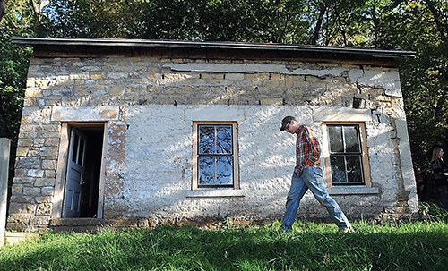 Caleb Wunderlich walks outside his stone house on Sixth Street in Mankato, Minn. Wunderilch is restoring the home, considered to be the oldest stone house in Mankato. (Pat Christman/The Free Press via AP)